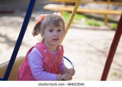 little girl sitting on a swing in children's park