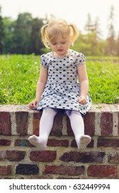 Little girl sitting on the wall, happy to be barefoot, she took her shoes off