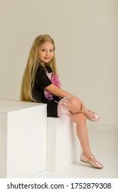 Little girl sitting on a white cube cross-legged.