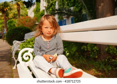 Little girl sitting on a white bench