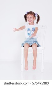 Little girl sitting on a white chair, playing, laughing and pulls hands. Studio shoot. Model portfolio.
