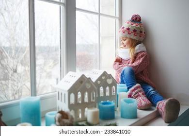 Little girl sitting on a window sill