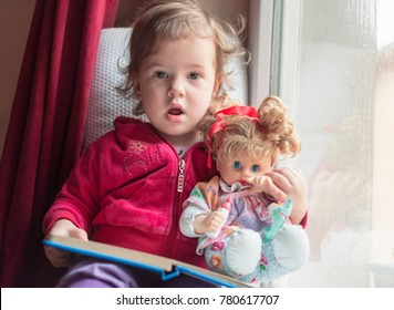 a little girl sitting on the window with her doll and reading a book together