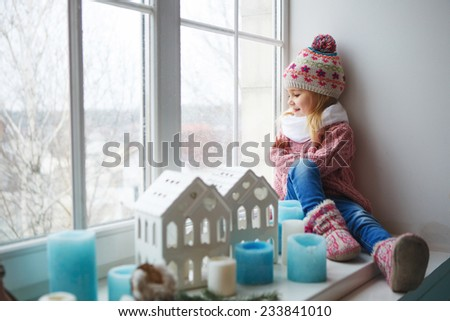 Little girl sitting on a window sill