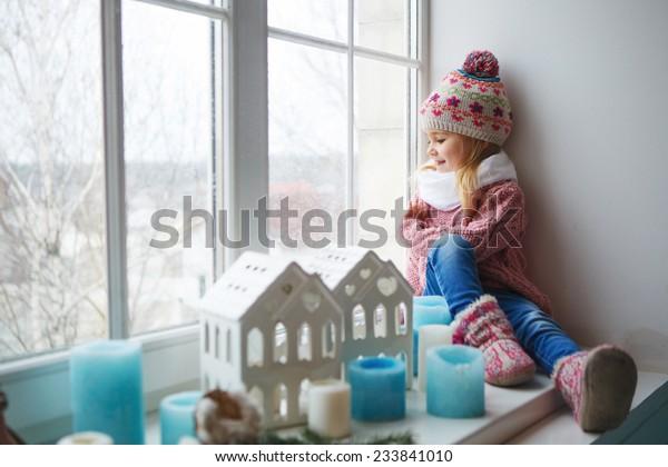 窓台に座っている小さな女の子