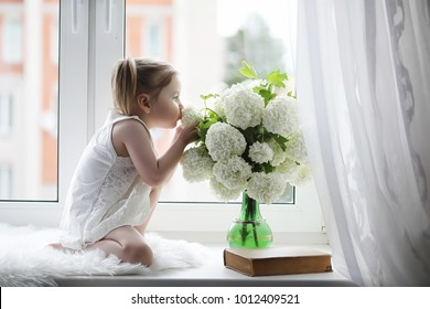 A little girl is sitting on the windowsill. A bouquet of flowers in a vase by the window and a girl sniffing flowers. A little princess in a white dress with a bouquet of white