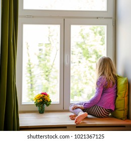 Little girl sitting on windowsill and looking out window