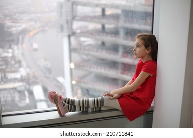 Little girl sitting on the windowsill of a large window on a cloudy day