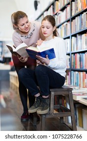 Little girl sitting on wooden stepladder choosing interesting book with mother in bookstore