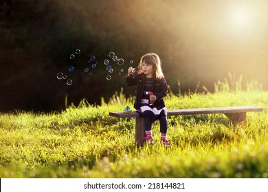 little girl sitting on a wooden bench blows bubbles in the rays