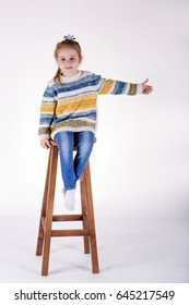 Little girl is sitting on a wooden chair