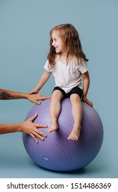 Little girl is sitting on a yoga ball, while helping hands holding ball still so she wouldn't fall. Her legs do not touch the floor. Over blue background.