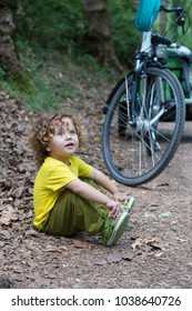 Little girl sitting in a path covered with leaves next to a bike. Autumn outdor scene