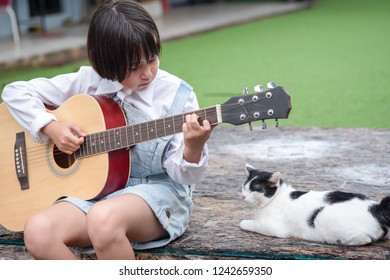 Little girl sitting playing guitar with cat.