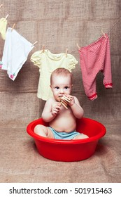 Little girl sitting in red pelvis and gnaws a wooden clothespin