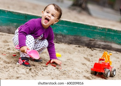 Little girl sitting in the sandbox and playing with molds on the playground The little child is playing in the sandbox
