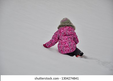 Little girl sitting in a snow