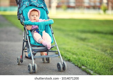 little girl sitting in a stroller. baby for a walk in a pram. child in summer outdoors