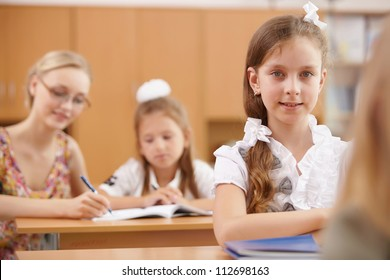 Little girl sitting and studying at school class