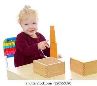 Little girl sitting at the table and collects a pyramid in Montessori school isolated on white background.The concept of development of the child, the child's upbringing.