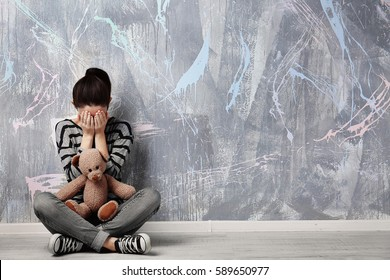 Little girl sitting with toy bear on color wall background