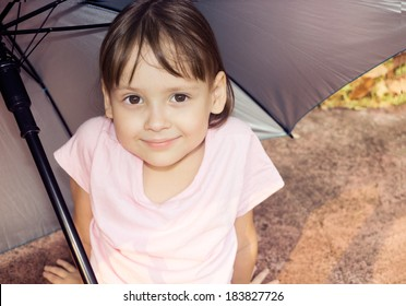 little girl sitting under umbrella and smiling