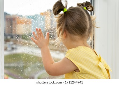 little girl is sitting at the window and is sad. children are bored at home due to quarantine and self-isolation