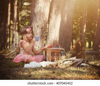 A little girl is sitting in the woods playing a card game with a teddy bear for an imagination or fairy tale concept.