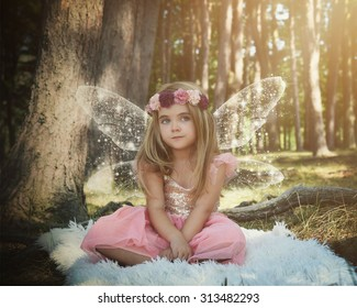 A little girl is sitting in the woods with sparkle fairy wings on pretending to be magical for an imagination or fairy tale concept.
