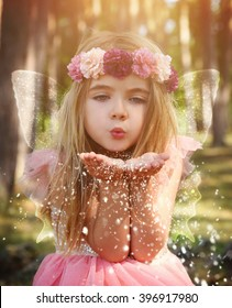A little girl is sitting in the woods with sparkle fairy wings blowing magical dust for an imagination or fairy tale concept.