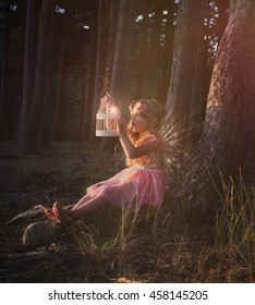 A little girl is sitting in the woods with sparkle fairy wings looking at a magical birdcage for an imagination or fantasy concept.