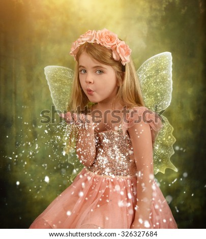 b9c6e684f8 A little girl is sitting in the woods with sparkle fairy wings blowing  magical dust for