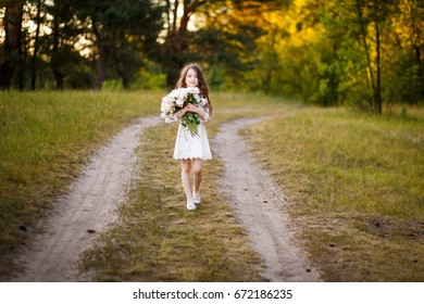 little girl six years old with brown hair and blue eyes with a bouquet of peony flowers wearing white dress, smiling