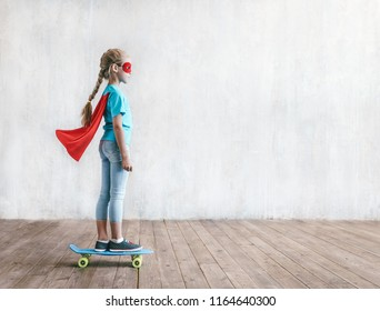 Little girl skating on a skateboard in studio