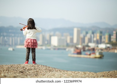 A little girl in a skirt stands on the high ground in the suburbs, and she plays the violin with her back to the camera.