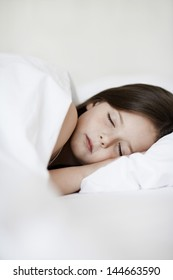 Little girl sleeping in bed cover with white blanket