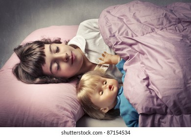 Little girl sleeping in bed with a doll