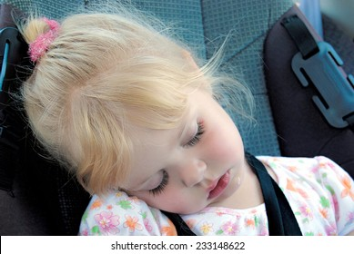little girl sleeping and drooling in a car seat with seat belt
