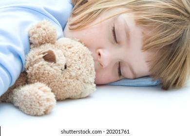 little girl sleeping and hugging her teddy bear