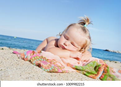 Little girl sleeping on beach near sea.