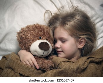 A little girl is sleeping with a toy bear. The child smiles in his sleep