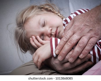 Little girl sleeping. Wrinkled hands of an adult man gently hug baby