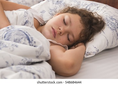 Little Girl Sleeps In a Bed On a White Background In The Morning Light.