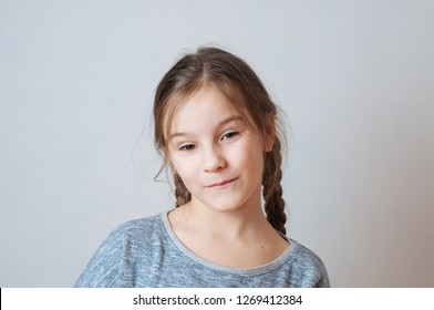 Little girl with a sly look and hair pigtail on a neutral background