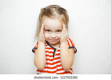 Little girl with sly smile slightly covers her face