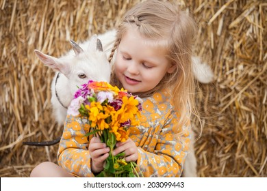 little girl with a small goat at the farm