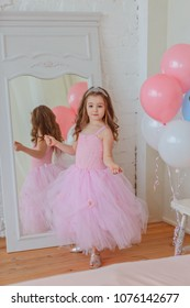 A little girl in a smart dress with a crown on her head is standing near the mirror