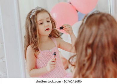 A little girl in a smart dress stands near the mirror and paints her lips / copy space