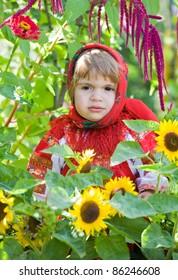 little girl in a smart Sarafan is among sunflowers