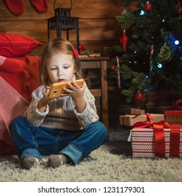 little girl with smartphone at home with a Christmas tree, presents and candles celebrating christmas
